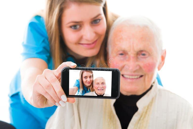 Paciente mayor y autorretrato joven del doctor fotografía de archivo libre de regalías