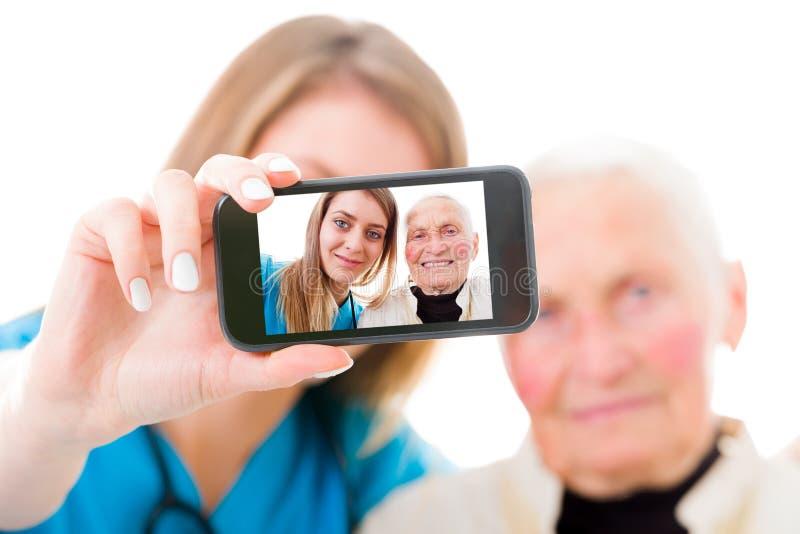 Paciente mayor y autorretrato joven del doctor imagen de archivo