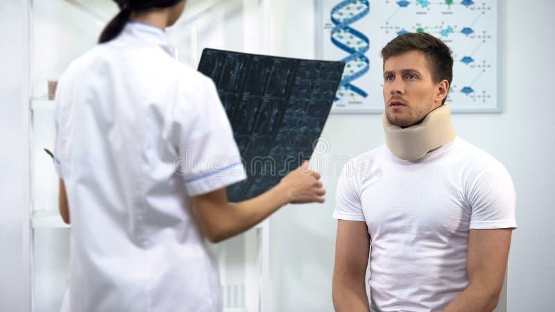 Paciente no colar cervical da espuma que escuta para medicar, guardando resultados do raio X fotografia de stock royalty free