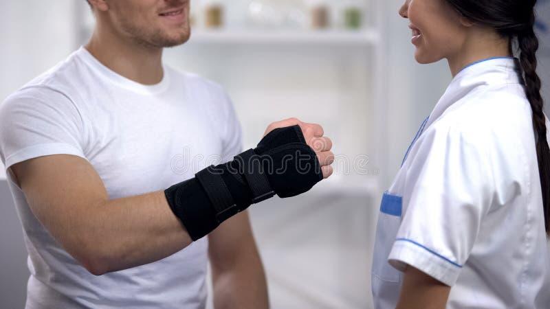 Paciente no doutor da mão da exibição da cinta do pulso do titã, reabilitação após a operação imagem de stock