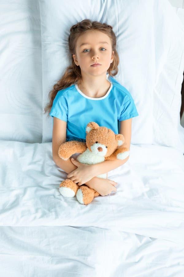 Paciente pequeno com o urso de peluche que encontra-se na cama no hospital fotos de stock royalty free