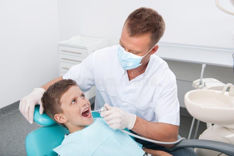 Paciente pequeno no escritório do dentista. imagens de stock royalty free