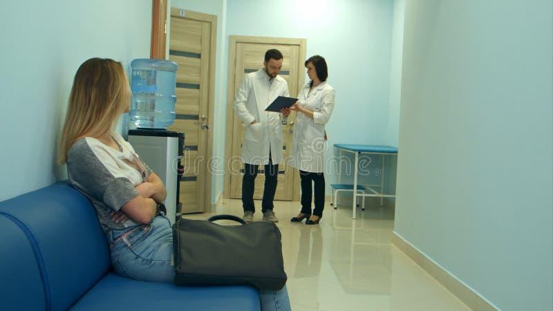 Paciente preocupado da mulher que espera no salão do hospital quando dois doutores que discutem o diagnóstico fotografia de stock