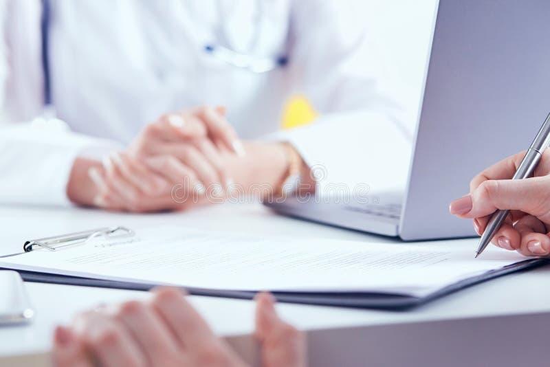 Paciente que assina o contrato médico O doutor fêmea explica como encher o formulário médico fotos de stock
