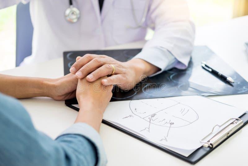 Paciente que es mano que se sostiene desesperada tranquilizadora por encoura del doctor fotos de archivo