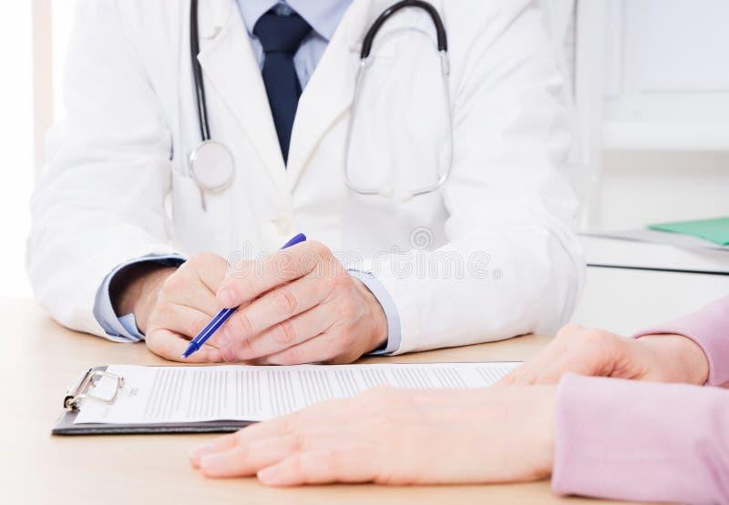 Paciente que escuta atentamente um doutor masculino que explica sintomas pacientes ou que faz uma pergunta como discutem o docume imagem de stock