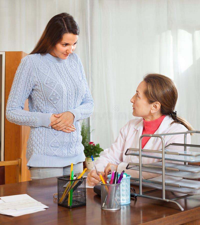 Paciente que habla con su doctor sobre enfermedad del estómago fotografía de archivo libre de regalías