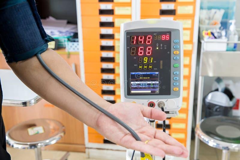 Paciente que mide la presión arterial antes de ver para el doctor imagen de archivo