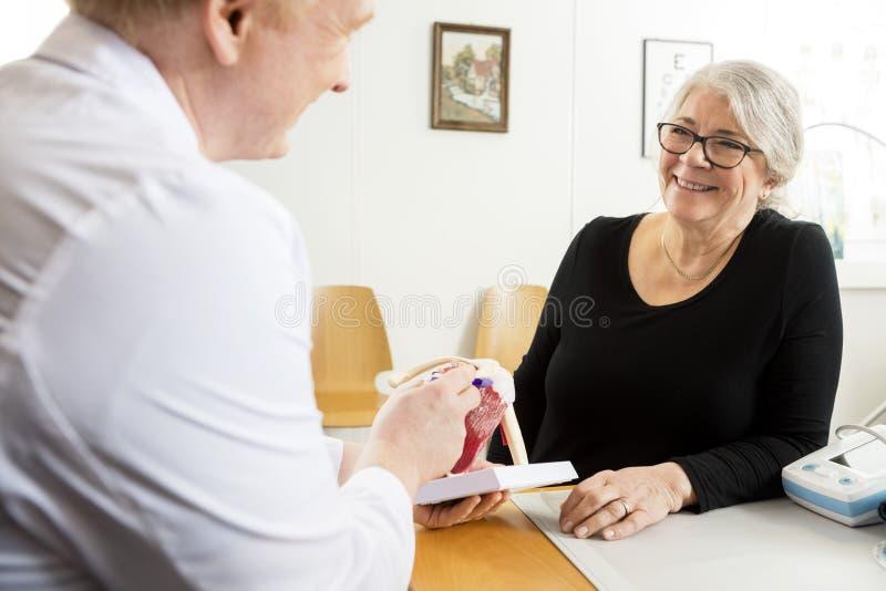 Paciente que mira el puño masculino del doctor Explaining Shoulder Rotator fotos de archivo libres de regalías