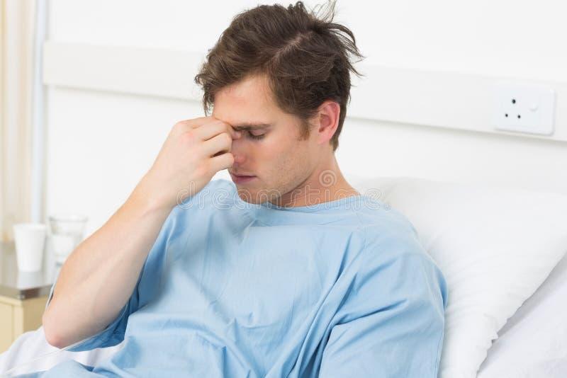 Paciente que sofre da dor de cabeça que relaxa no hospital fotografia de stock