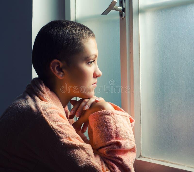 Paciente que sofre de câncer nova que está na frente da janela do hospital foto de stock royalty free