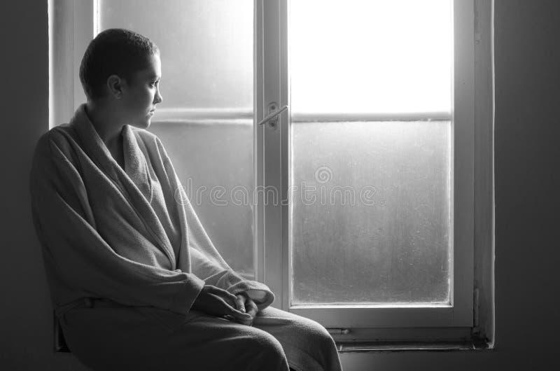 Paciente que sofre de câncer nova que senta-se na janela do hospital imagens de stock
