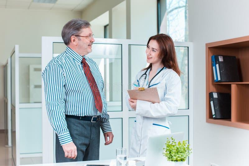 Paciente que sorri a seu doutor no escritório médico imagem de stock royalty free