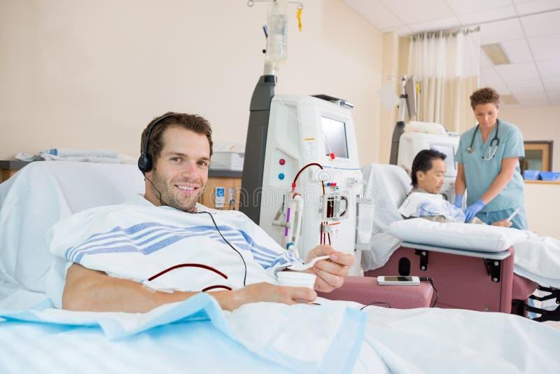 Paciente que sostiene el vidrio de hielo machacado durante renal fotografía de archivo libre de regalías