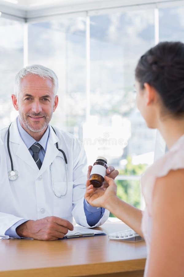 Paciente que sostiene una botella de píldoras delante del doctor imágenes de archivo libres de regalías