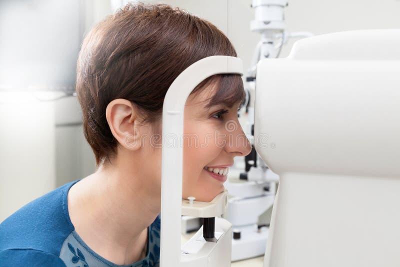 Paciente sonriente de la mujer que tiene un examen del refractor fotos de archivo libres de regalías
