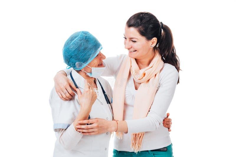 Paciente sonriente que abraza al doctor foto de archivo