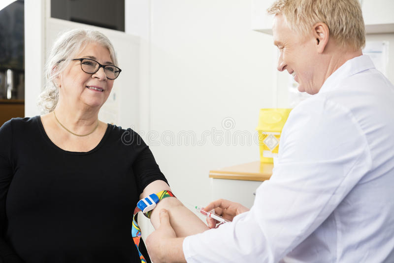 Paciente sonriente que mira al doctor de sexo masculino Collecting Blood In Syrin fotos de archivo libres de regalías