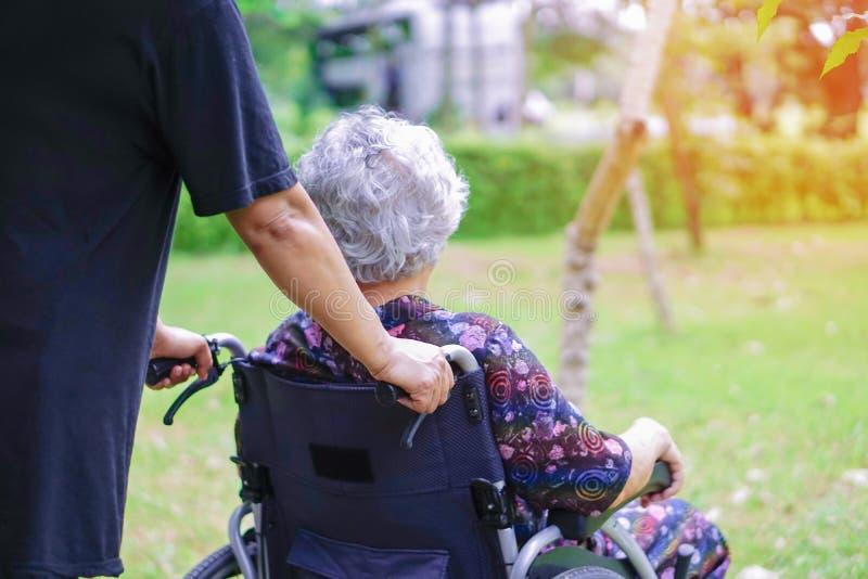 Paciente superior ou idoso asiático da mulher da senhora idosa com cuidado, ajuda e apoio na cadeira de rodas no parque fotografia de stock