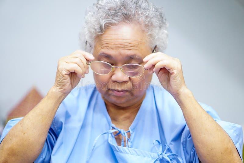 Paciente superior ou idoso asiático da mulher da senhora idosa com monóculos ao sentar-se na cama na divisão de hospital de nu imagem de stock royalty free
