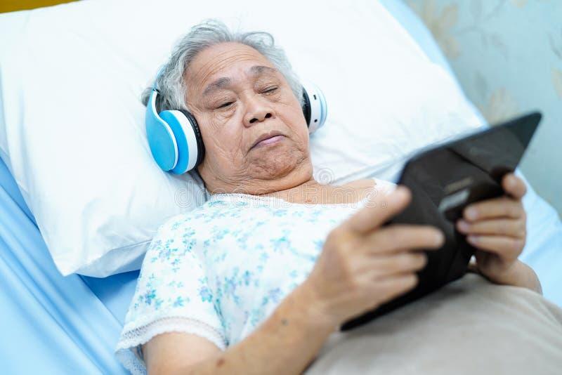 Paciente superior ou idoso asiático da mulher da senhora idosa que realiza em sua tabuleta digital das mãos e para escutar música fotografia de stock royalty free