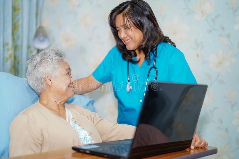 Paciente superior ou idoso asiático da mulher da senhora idosa que usa o laptop e o sorriso com doutor ao sentar-se na cama no ho foto de stock royalty free