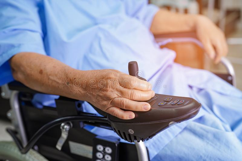 Paciente superior ou idoso asi?tico da mulher da senhora idosa na cadeira de rodas el?trica com controlo a dist?ncia na divis?o d fotografia de stock royalty free