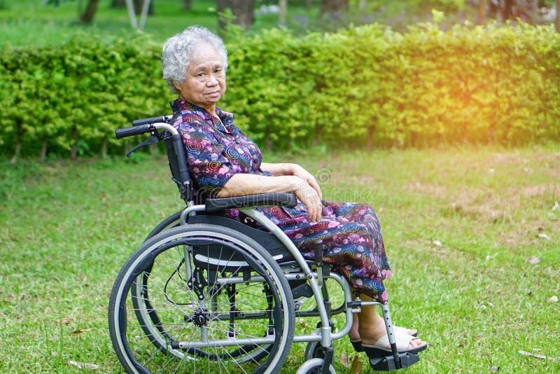 Paciente superior ou idoso asi?tico da mulher da senhora idosa na cadeira de rodas no parque fotografia de stock
