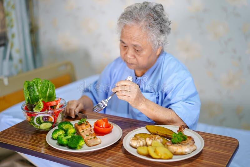 Paciente superior ou idoso asi?tico da mulher da senhora idosa que come o alimento saud?vel do caf? da manh? com esperan?a e feli fotografia de stock royalty free
