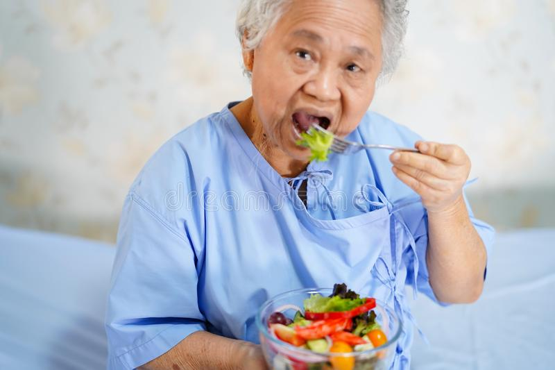 Paciente superior ou idoso asi?tico da mulher da senhora idosa que come o alimento saud?vel do caf? da manh? com esperan?a e feli fotos de stock