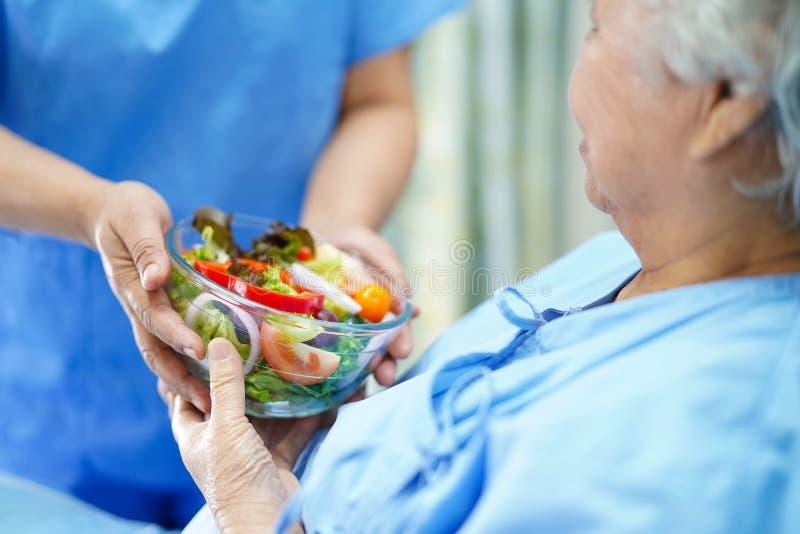 Paciente superior ou idoso asi?tico da mulher da senhora idosa que come o alimento saud?vel do caf? da manh? com esperan?a e feli imagem de stock royalty free