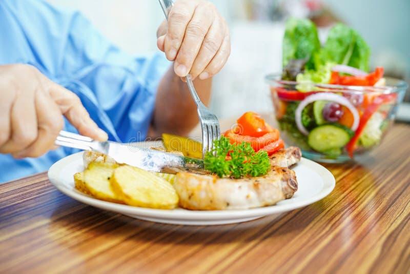 Paciente superior ou idoso asi?tico da mulher da senhora idosa que come o alimento saud?vel do caf? da manh? foto de stock royalty free