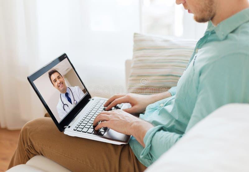 Paciente teniendo llamada video con el doctor en el ordenador portátil imagen de archivo