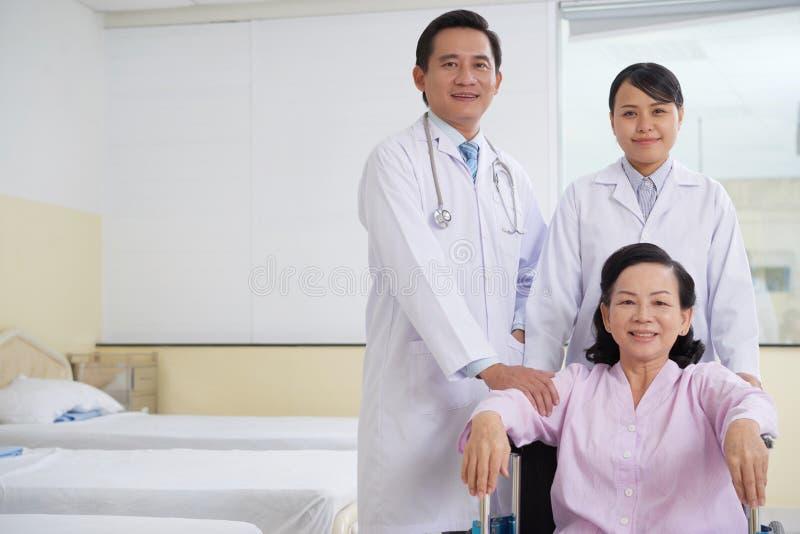 Paciente y doctores asiáticos en sala de hospital fotos de archivo