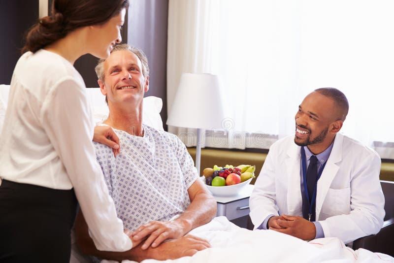 Paciente y esposa del doctor Talking To Male en cama de hospital foto de archivo