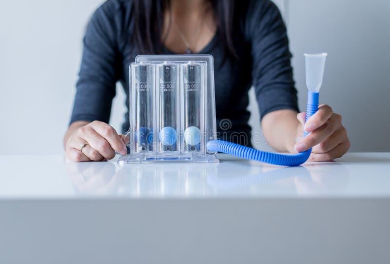 Pacientes asiáticos de la mujer que usan incentivespirometer o tres bolas para la respiración paciente profunda foto de archivo libre de regalías