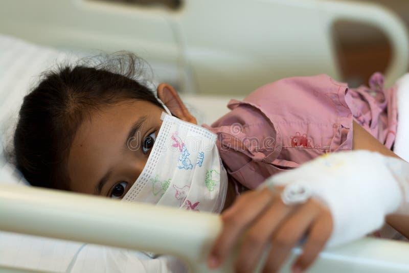 Pacientes da menina que vestem a máscara protetora no hospital imagens de stock