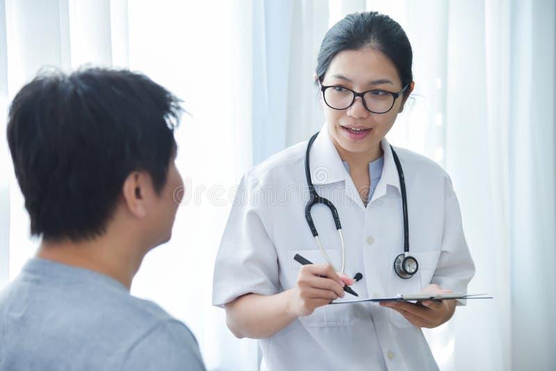 Pacientes masculinos de examen del doctor de sexo femenino imagen de archivo