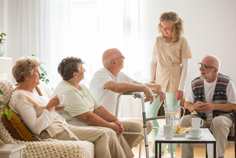 Pacientes mayores con la enfermera joven útil en la clínica de reposo imágenes de archivo libres de regalías