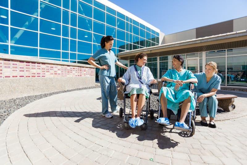 Pacientes na cadeira de rodas pelo hospital exterior das enfermeiras foto de stock