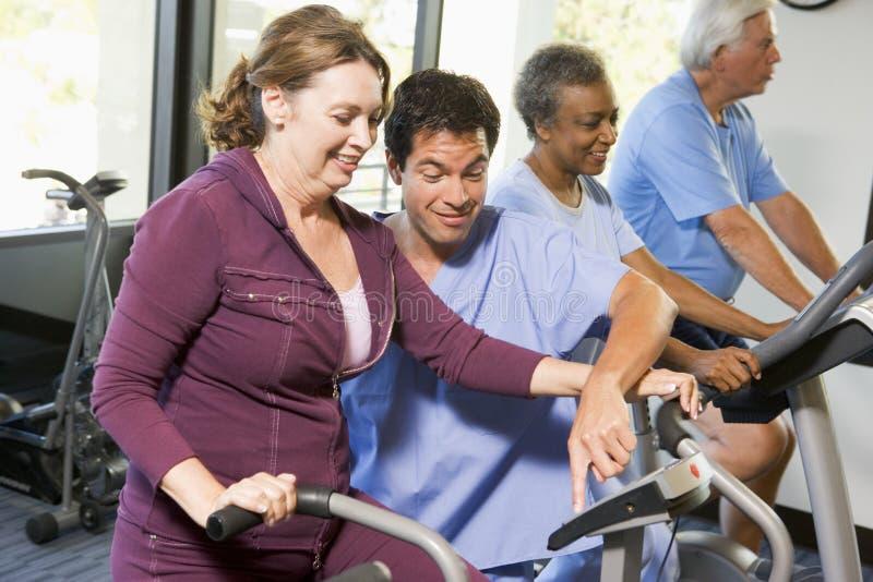 Pacientes na reabilitação com máquinas do exercício fotos de stock royalty free