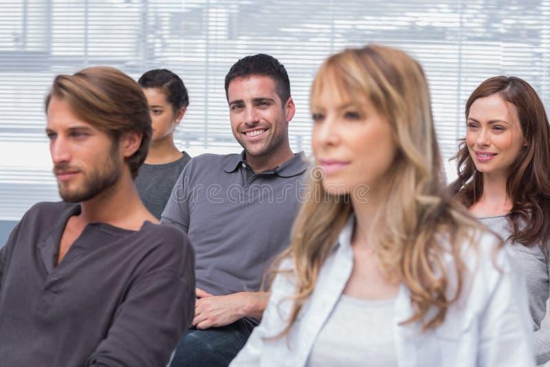 Pacientes que escutam na terapia do grupo com um sorriso do homem imagem de stock