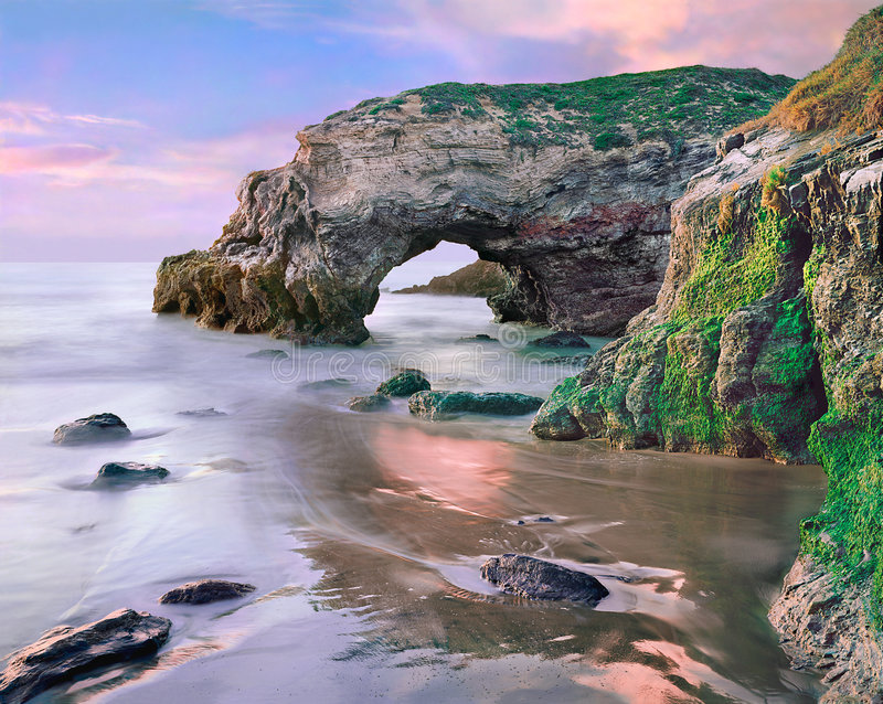 Pacific Arch. A natural arch along the Pacific coastline near Santa Maria, California. Image made during an extreme low tide at sunset stock photography