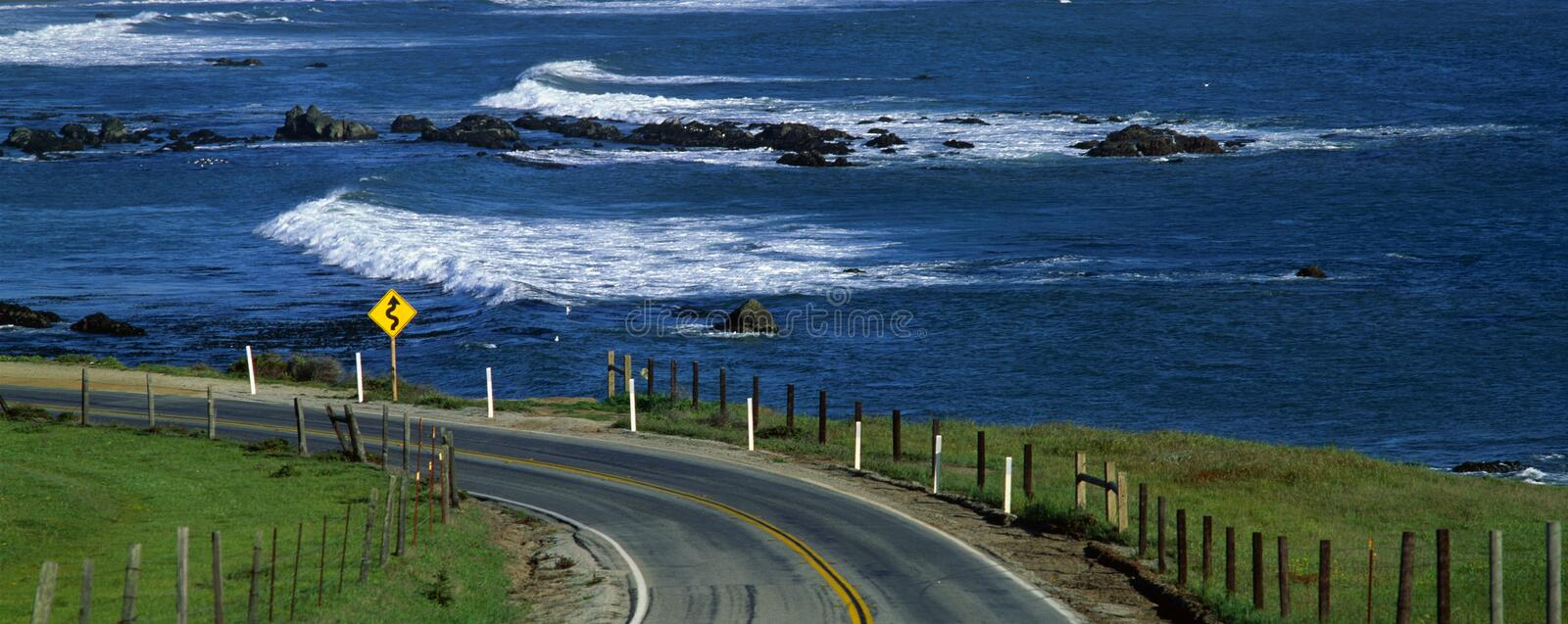 Pacific Coast Highway with ocean, CA. This is Route 1, also known as the Pacific Coast Highway. The ocean is to the right of the road which curves around a bend stock photos