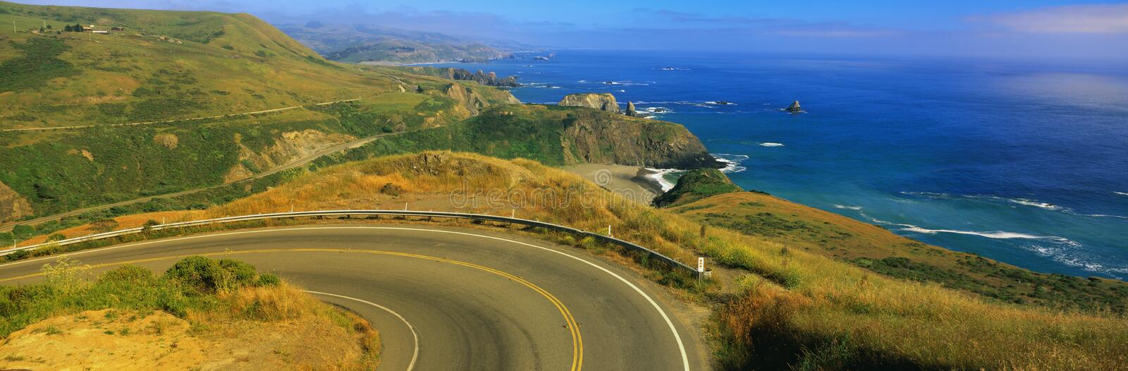 Pacific Coast Highway and ocean, CA. This is Route 1 also known as the Pacific Coast Highway. The road curves around a bend to the left and drops down stock images