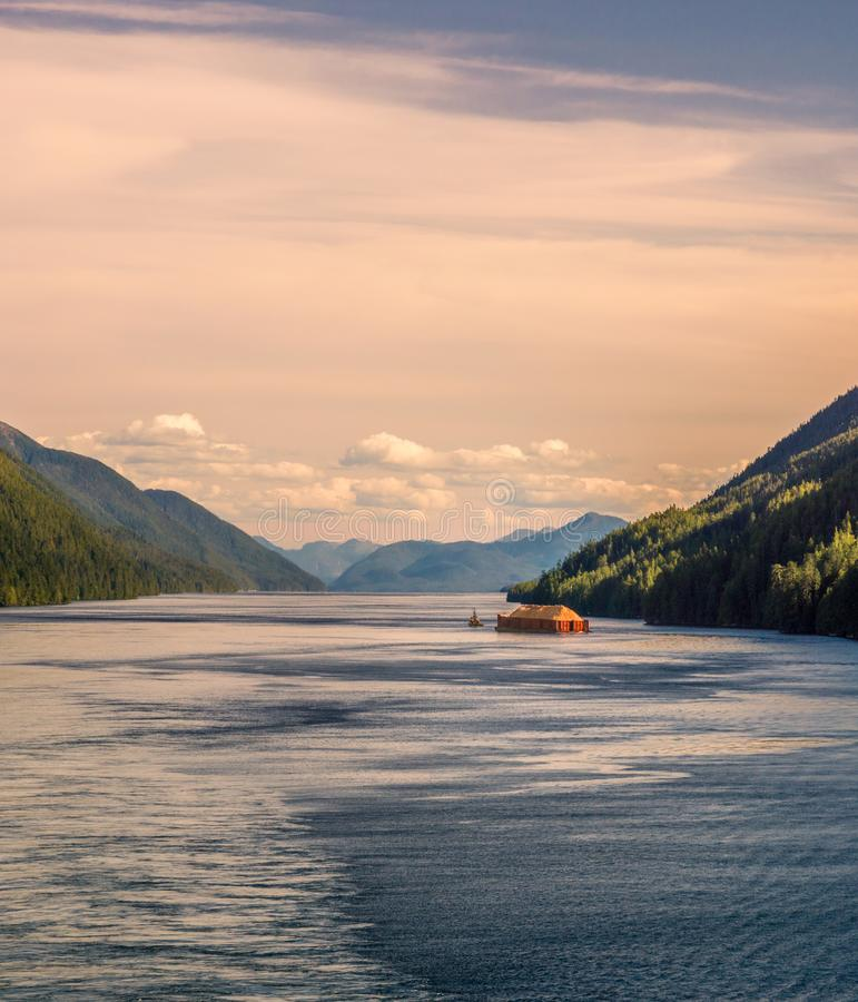 Pacific coast tugboat pulling barge, Principe Channel, British Columbia, Canada. Pacific coast tugboat pulling barge loaded with wood fiber in beautiful late royalty free stock photo
