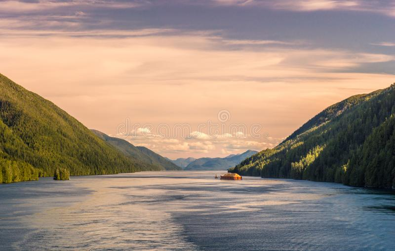Pacific coast tugboat pulling barge, Principe Channel, British Columbia, Canada. Pacific coast tugboat pulling barge loaded with wood fiber in beautiful late stock images