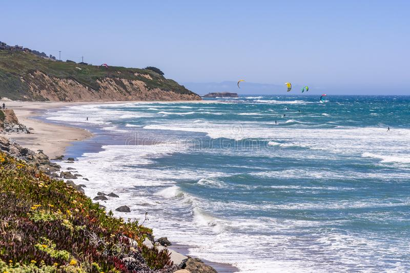 The Pacific Ocean coastline close to Santa Cruz, California; unidentified people windsurfing on a sunny day at Waddell Beach royalty free stock image