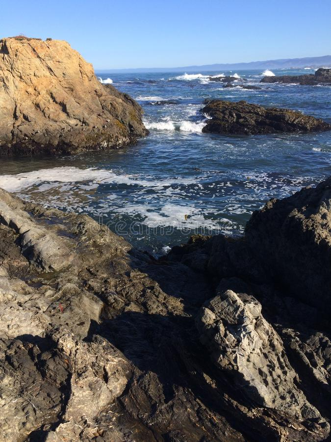 Pacific Ocean beside Fort Bragg. Rocky coastline at Fort Bragg, United States of America, with breaking waves extending to the horizon and pale blue sky stock image