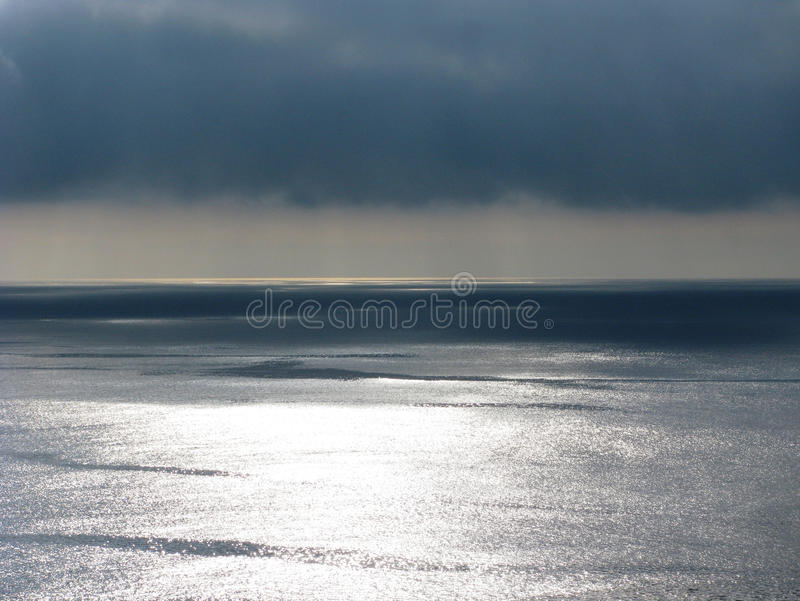 Pacific ocean sea and cloudscape with ominous clouds. Pacific ocean horizon with ominous clouds and sunlight reflecting on calm water stock image